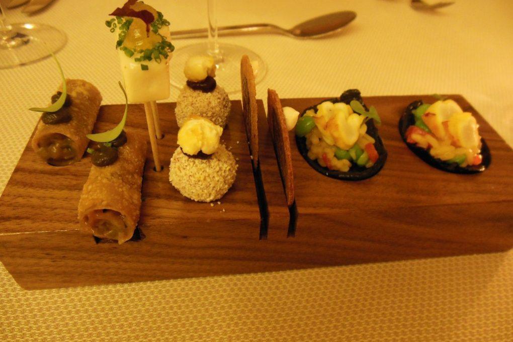 L`étable – Amuse guele I: Cannelloni mit asiatischem Gemüse, Geflügelleberpraline mit Portwein und Popcorn, Blutwurt-Chip, Paella auf Reis-Chip